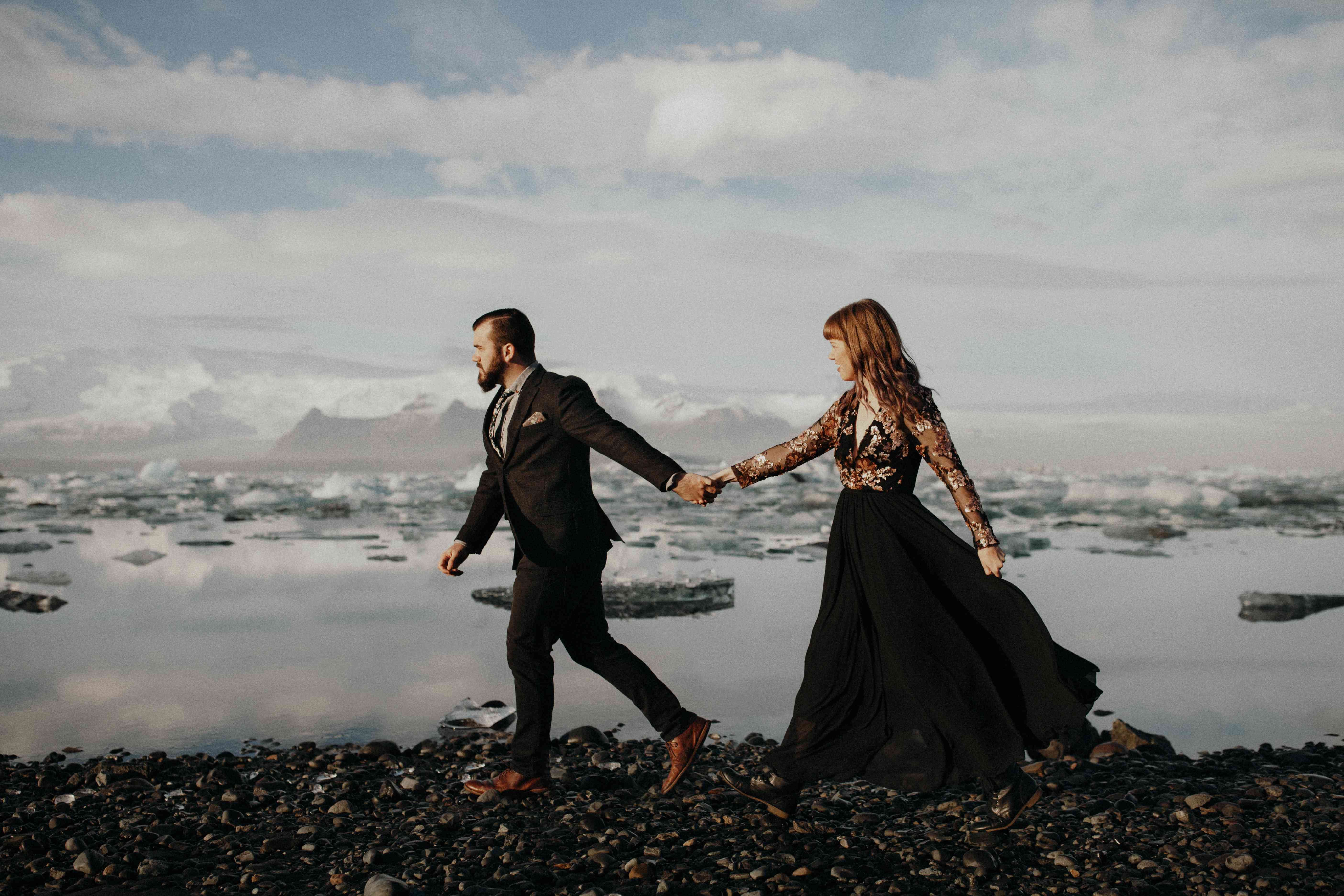 Couple walking next to an iceberg field in Iceland