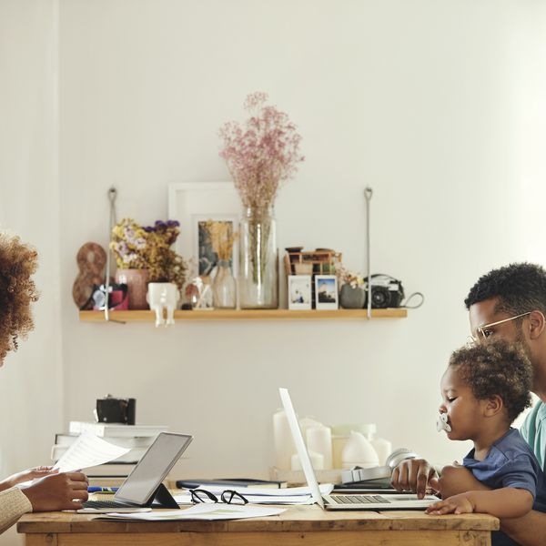couple working together at the dining room table with a toddler