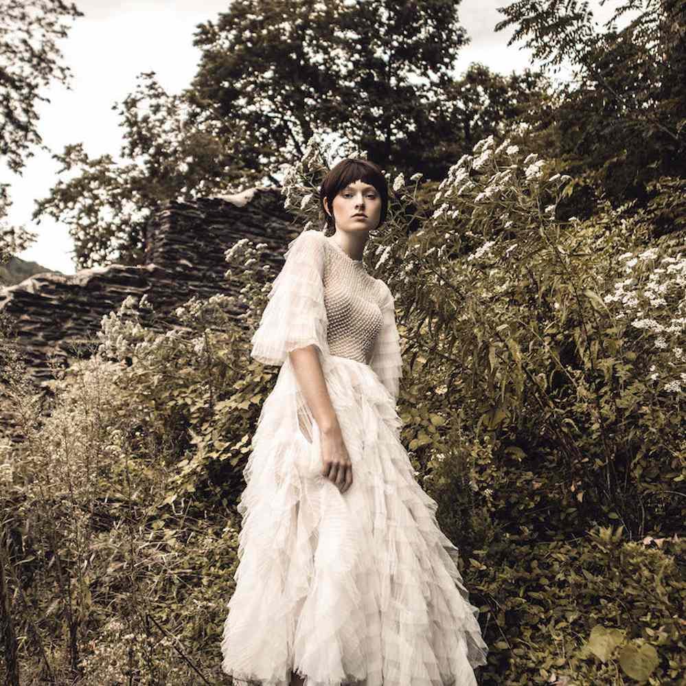 Model wearing Elaya Vaughn tulle wedding gown outside in greenery