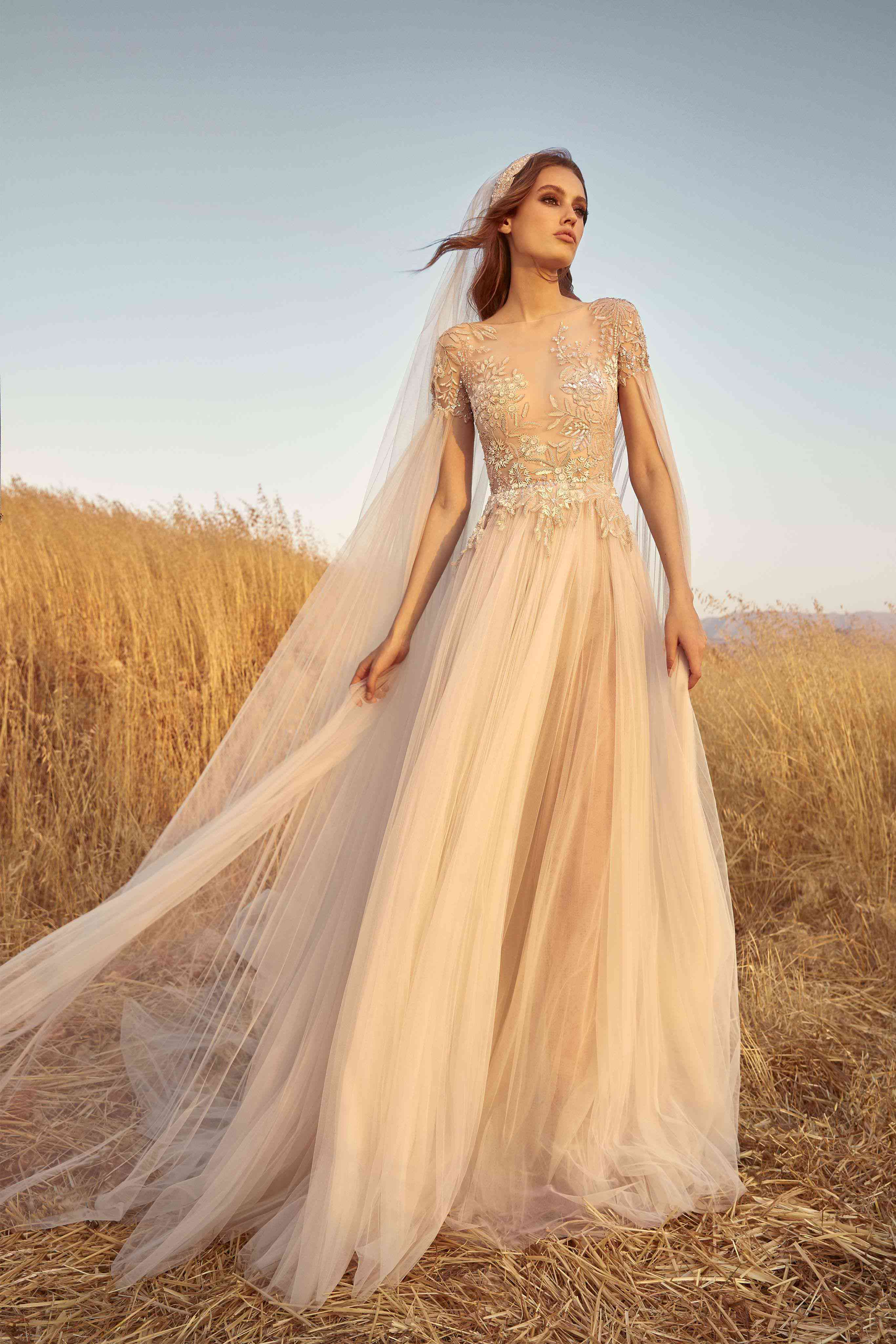 Model in a Flared, pleated sand dollar tulle dress with embroidered bodice and dramatic long pleated cape-like tulle sleeves and matching headpiece