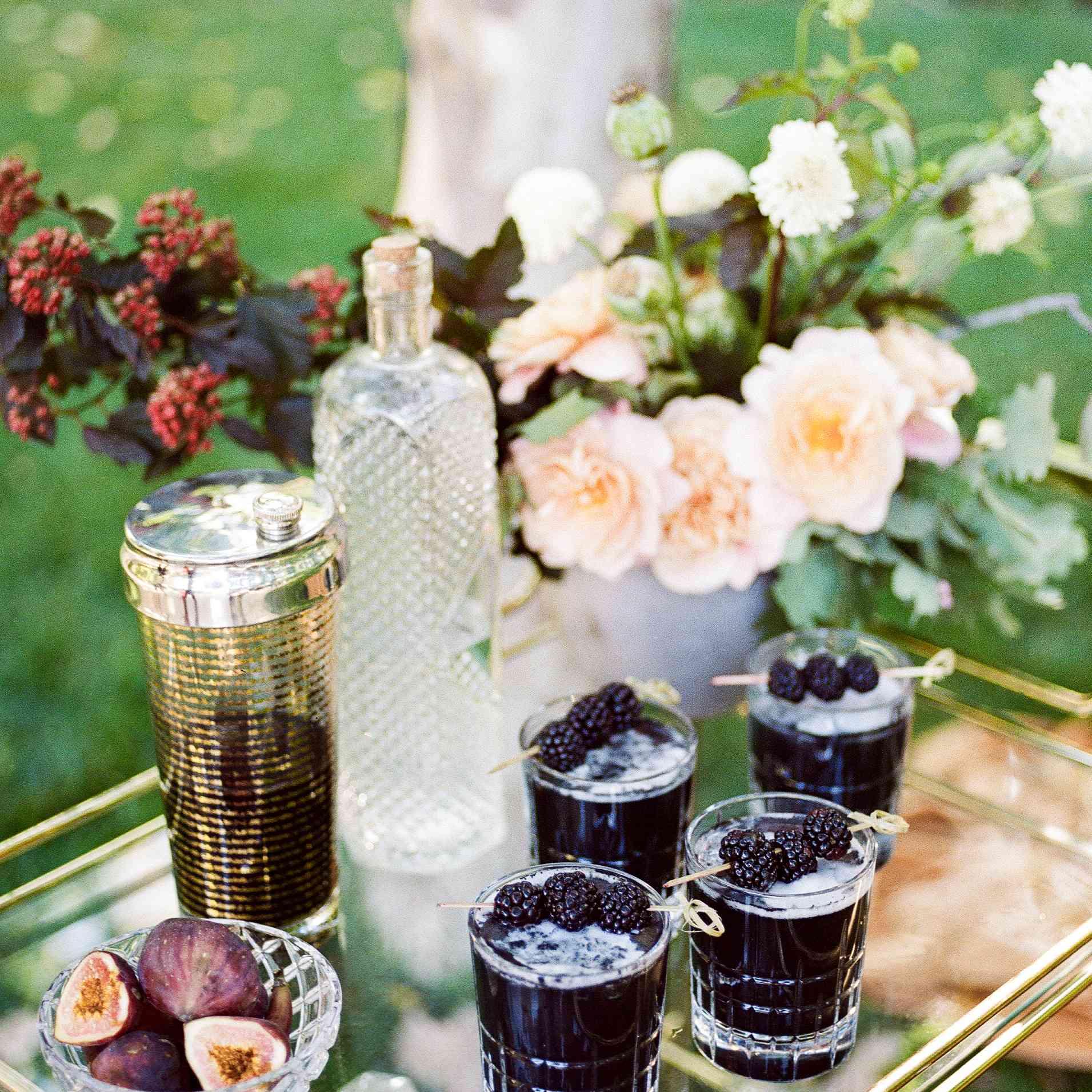 Blackberry-infused cocktails and floral arrangement on a glass bar cart