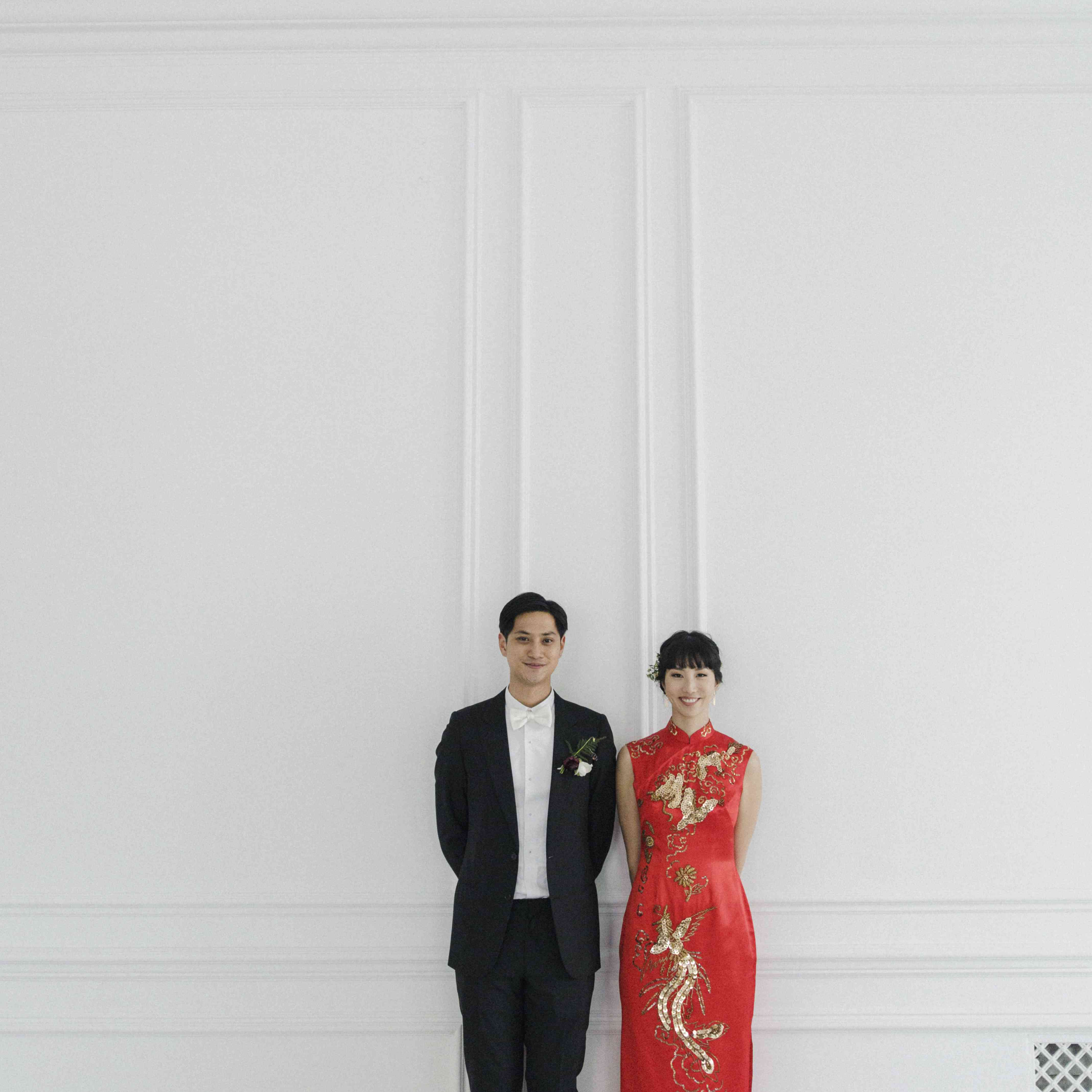 Bride and groom against white wall