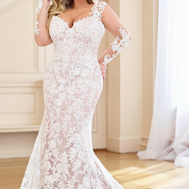 Plus size model in long lace overlay wedding gown with illusion sleeves
