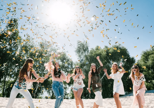 Girls dancing in confetti in the sand