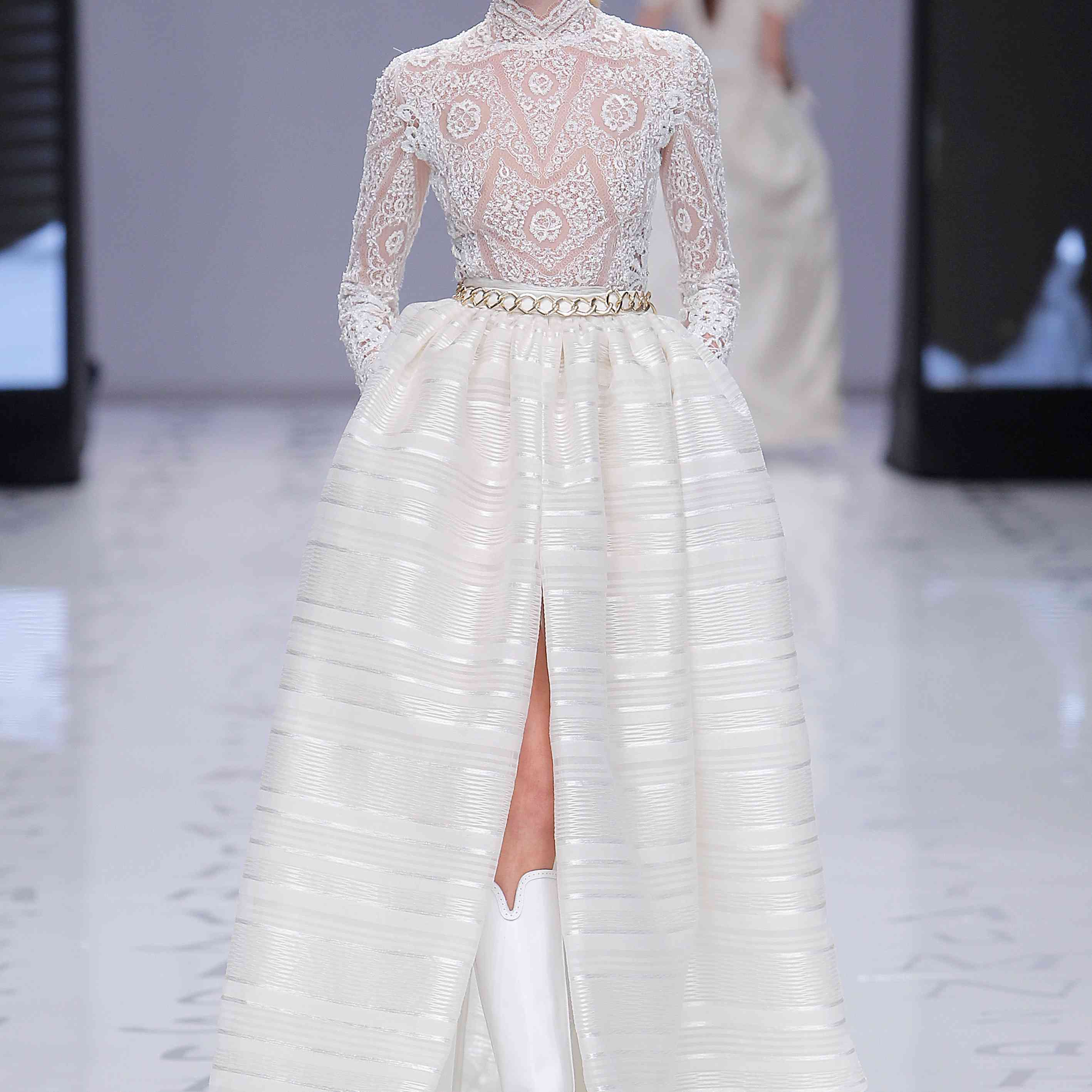 Model in a long-sleeved lace top with a striped organza full skirt with a front slit and a gold chain belt