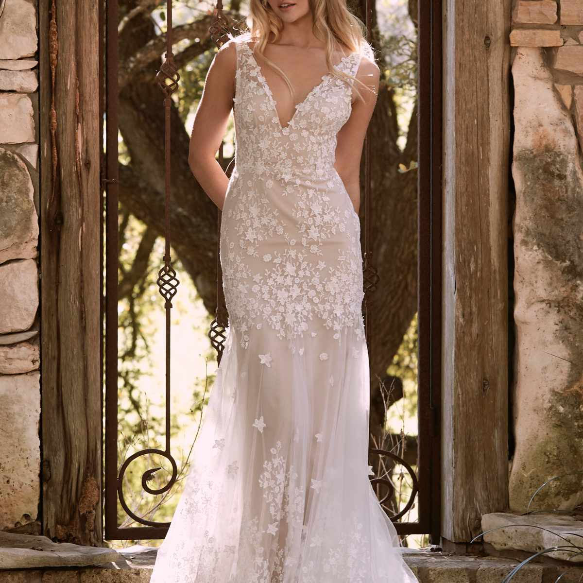 Model in V-neck fit and flare gown with floral lace appliques