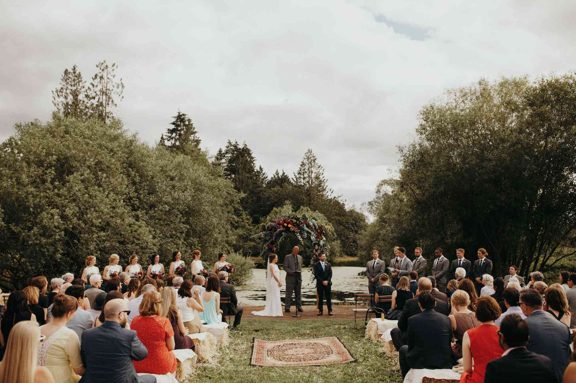 Wedding ceremony with guests sitting on hay bales and Persian rugs lining the aisle