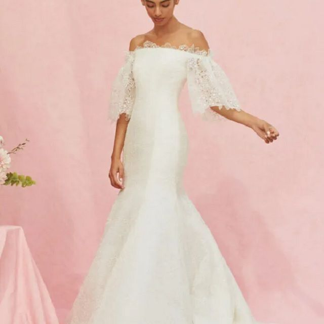 Model in lacy fit-and-flare, off-the-shoulder gown with half sleeves