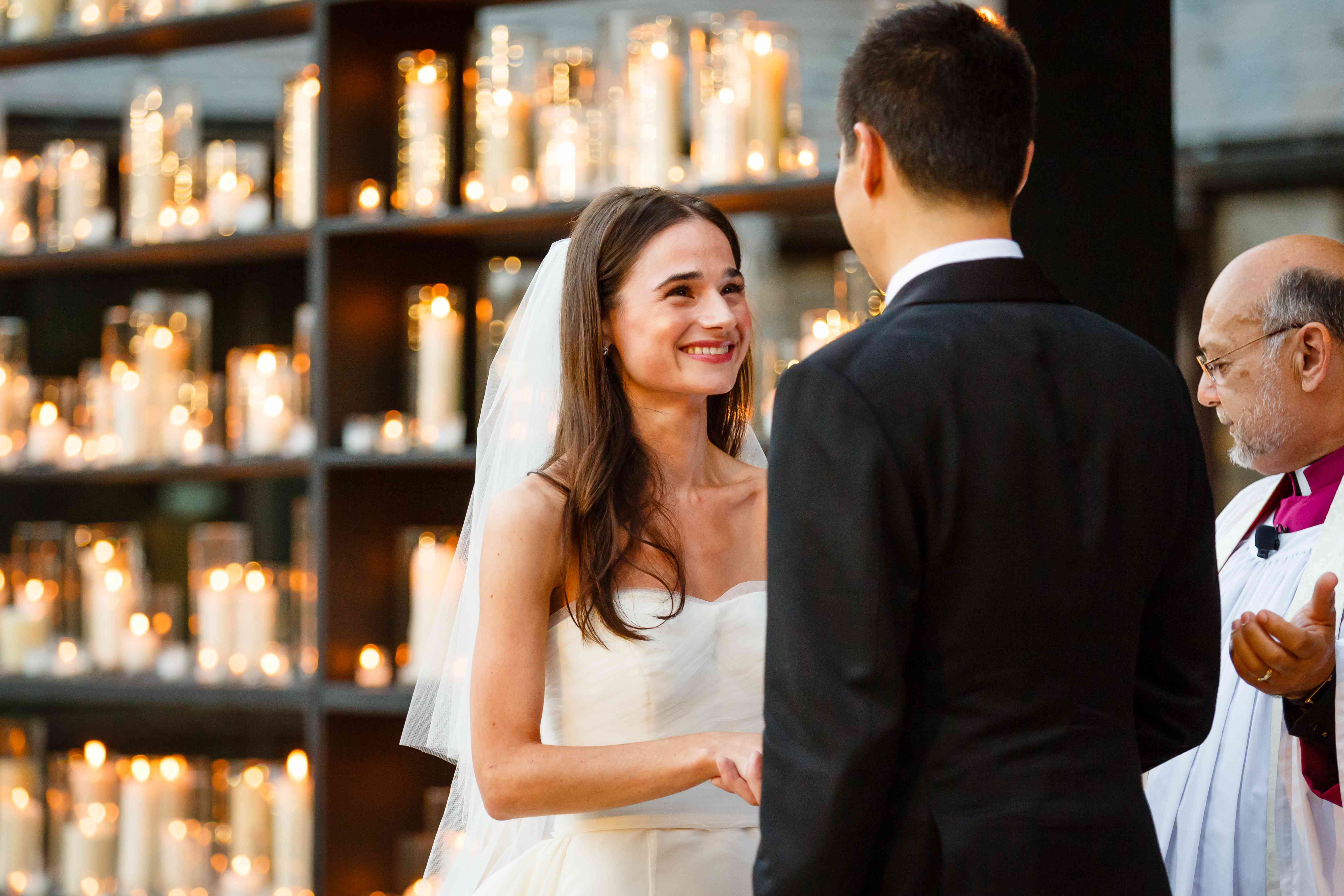 bride and groom at candlelit altar