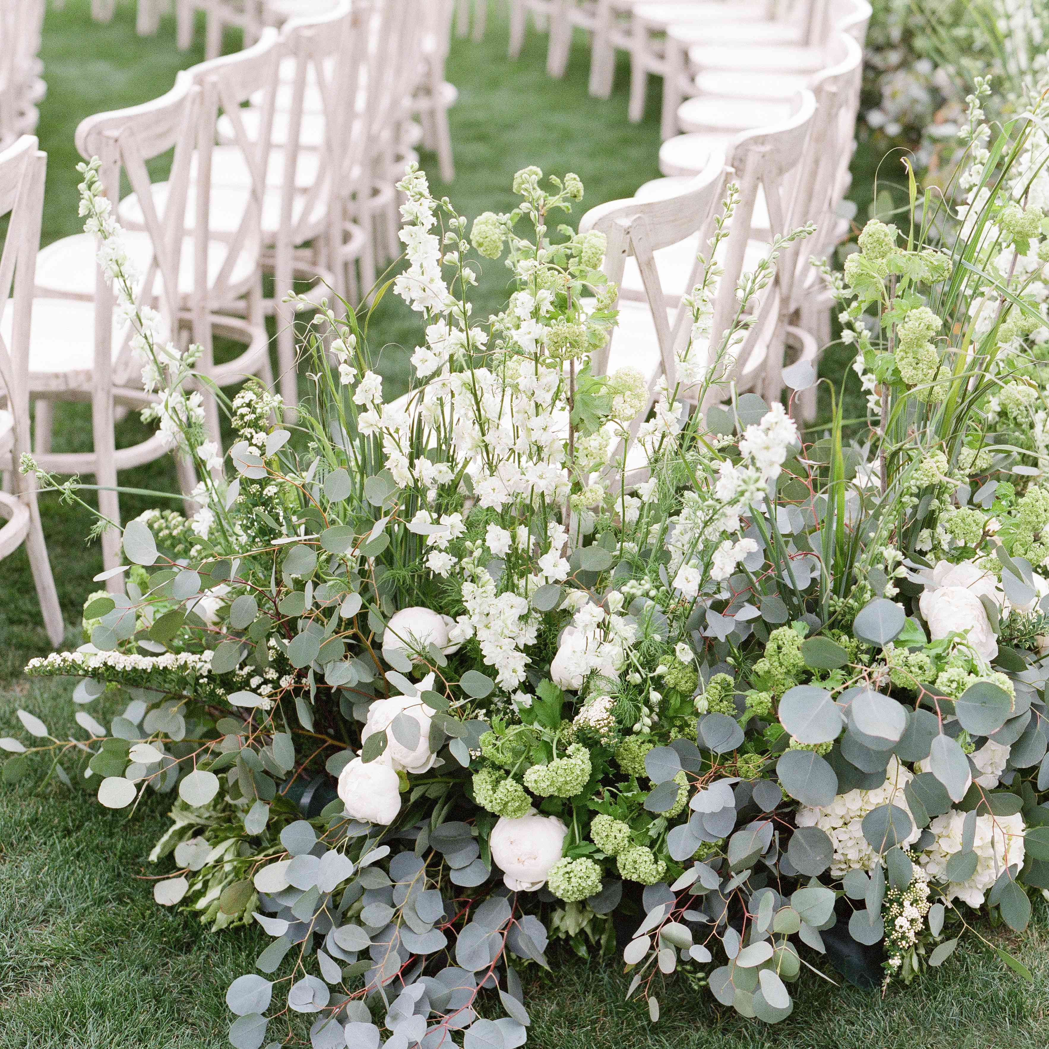 Side of a wedding aisle row with planted greenery and florals