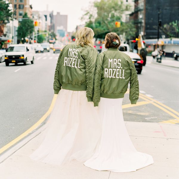 Two brides standing on the sidewalk in NYC wearing matching green jackets with