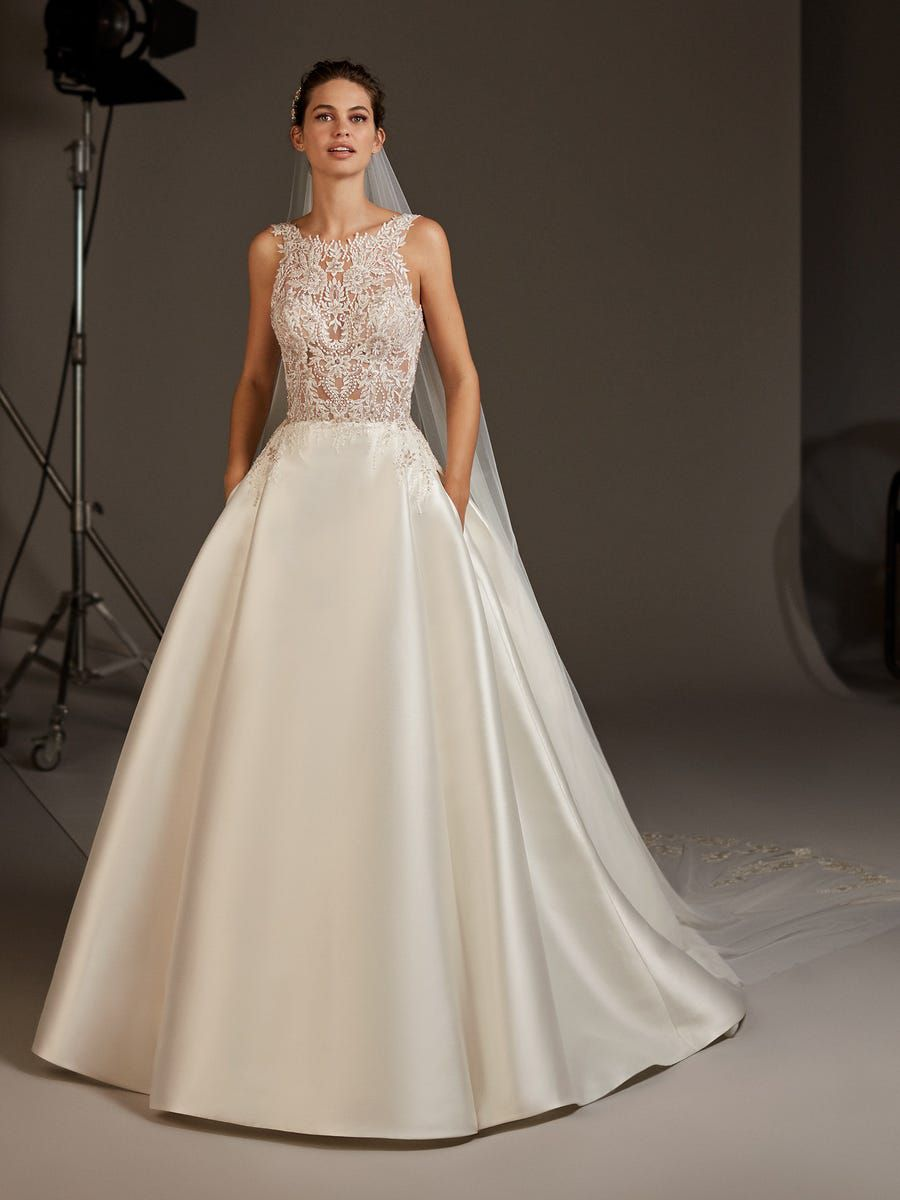 Model in princess gown style wedding dress with lace top and skirt pockets