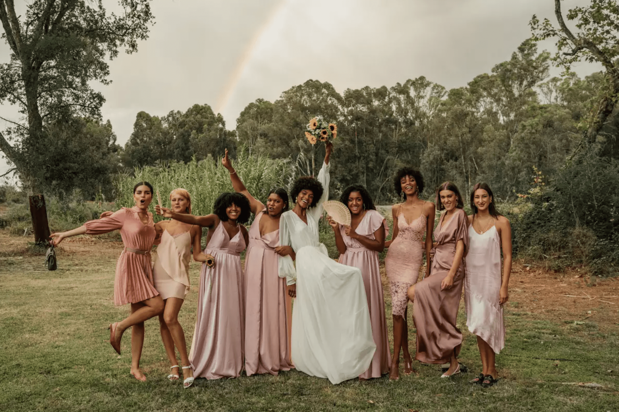 Bride and bridesmaids in blush posing in front of rainbow