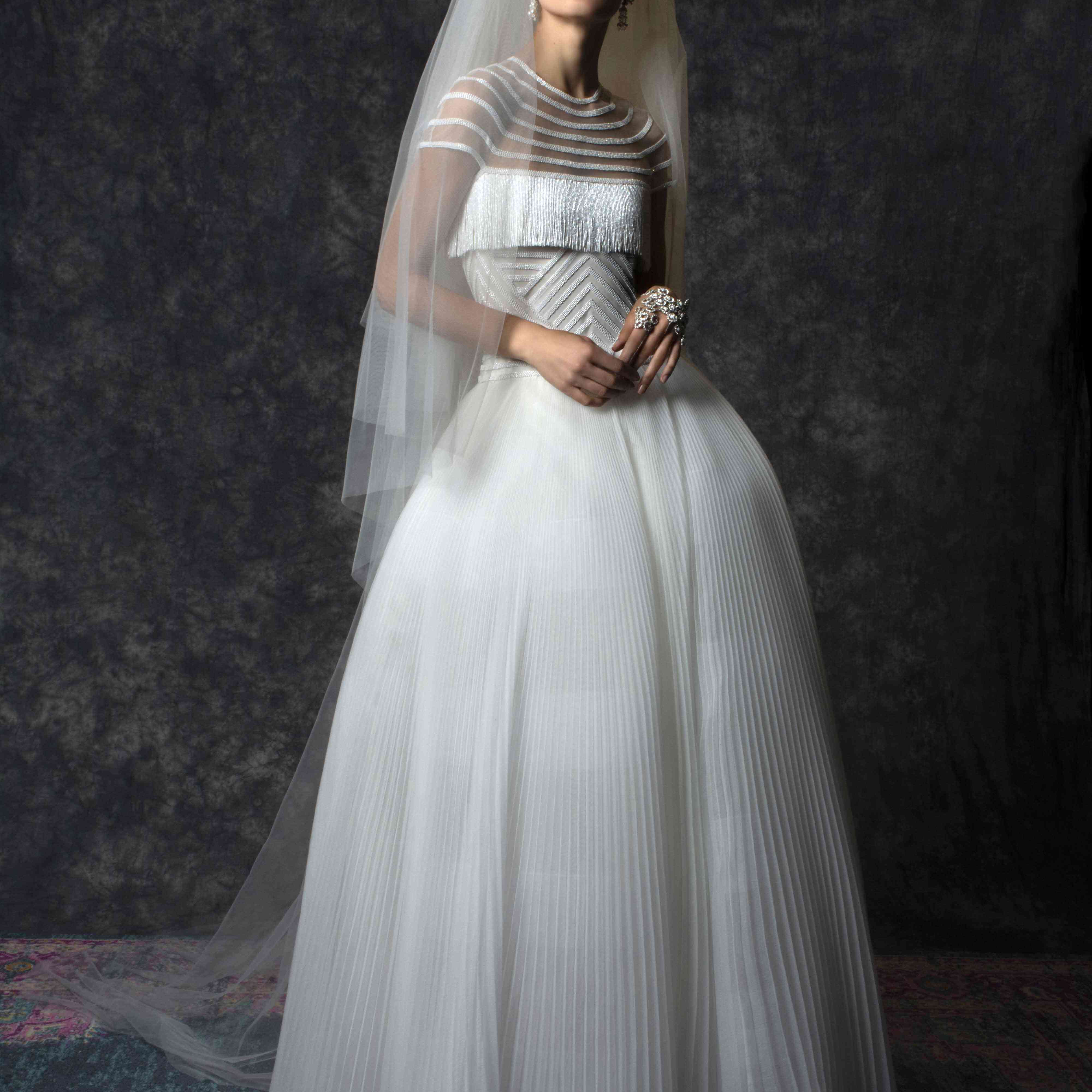 Model in tulle ballgown with geometric beading and fringe on the bodice