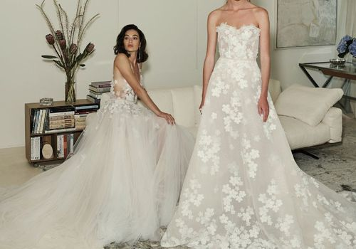 One model sitting and one standing in living room wearing wedding gowns