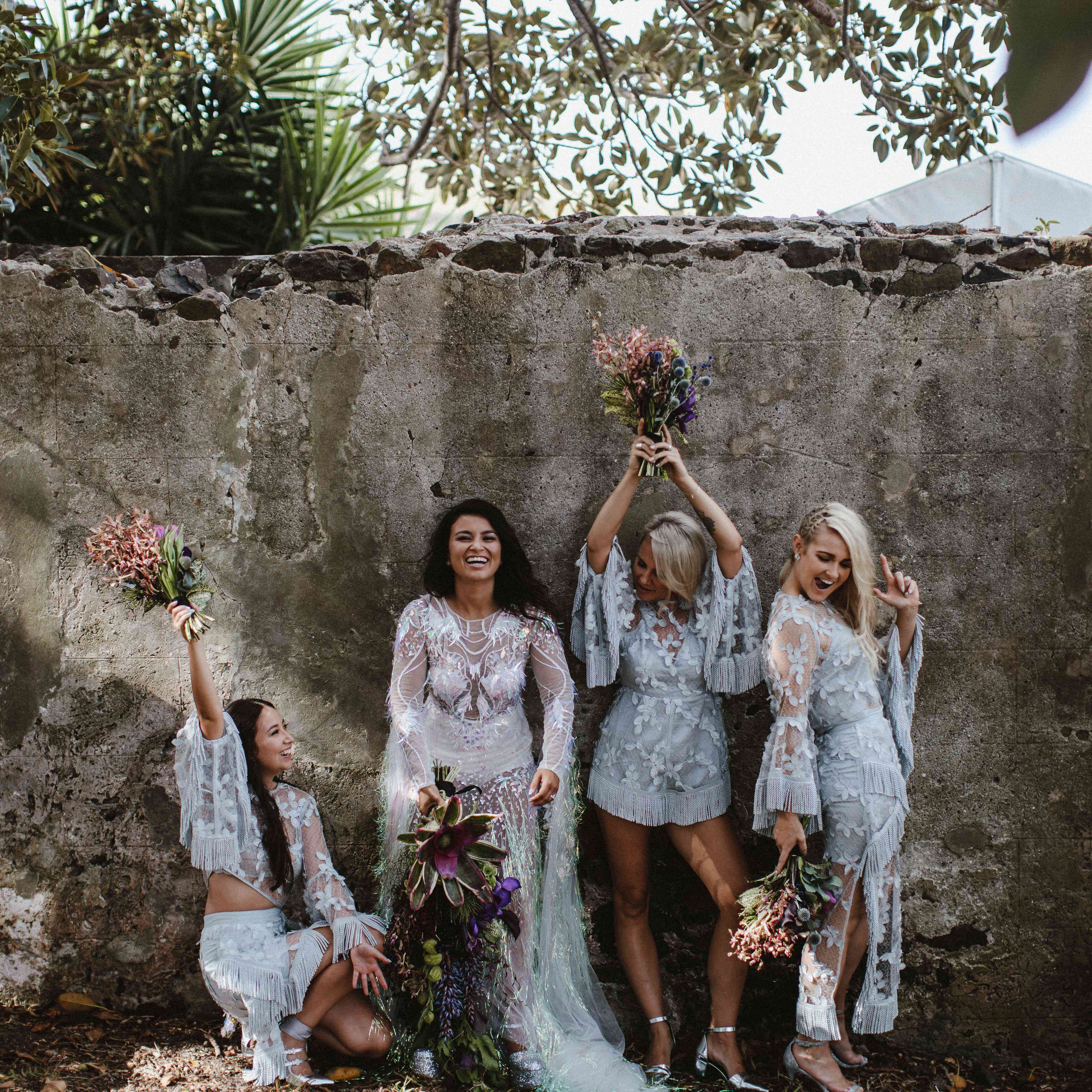 The bridesmaids are wearing silhouettes covered in fringe and appliques.