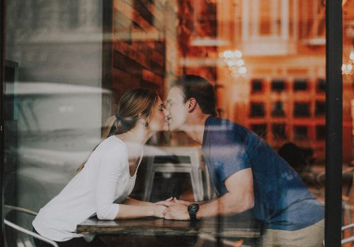 couple in love kissing behind a window in a cafe