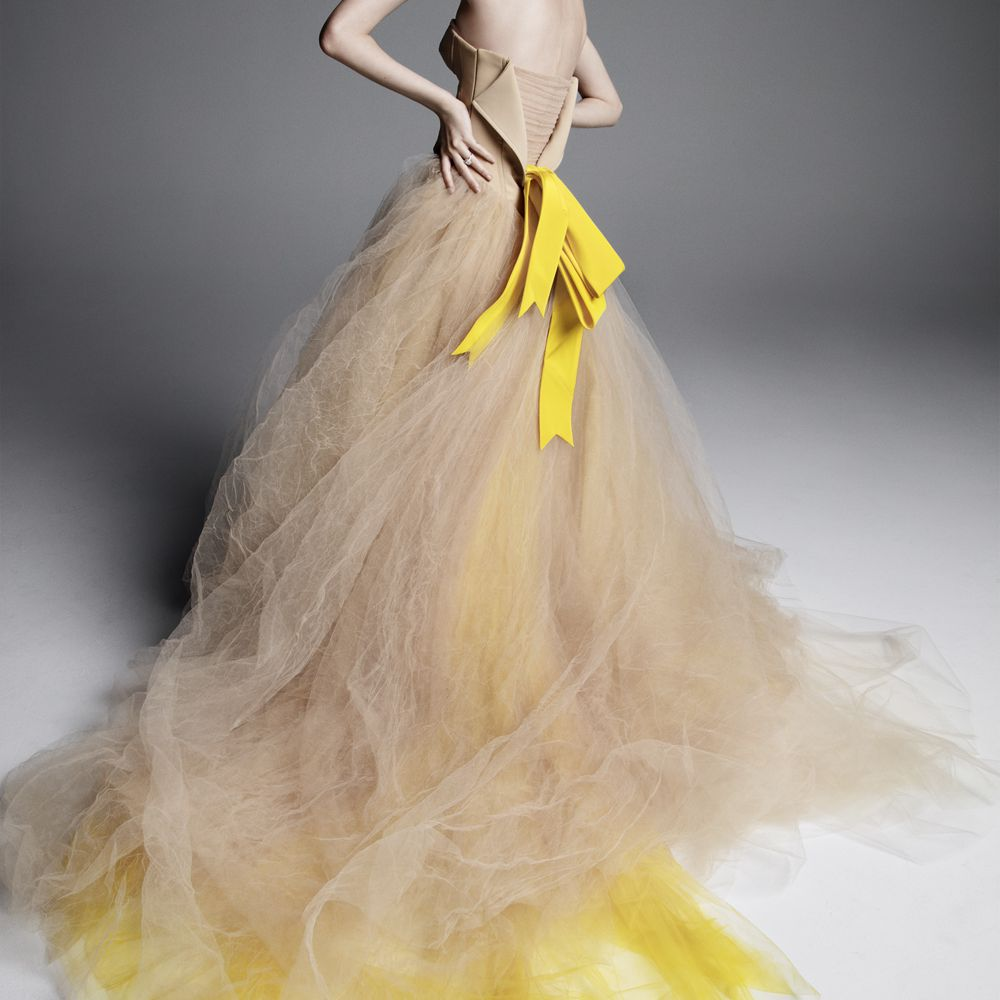 Model in strapless nude ballgown with a yellow and nude tulle skirt and a yellow bow at the back