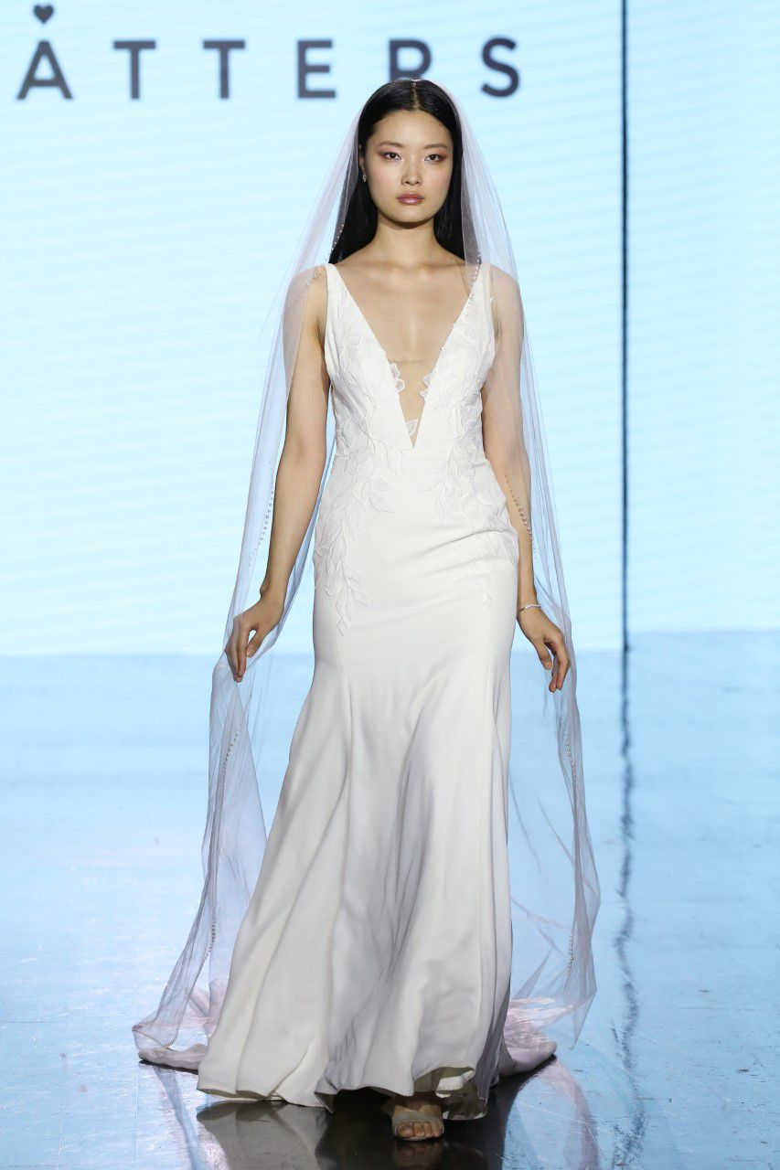 Model on runway in sleeveless wedding dress with a plunging neckline and lace appliques
