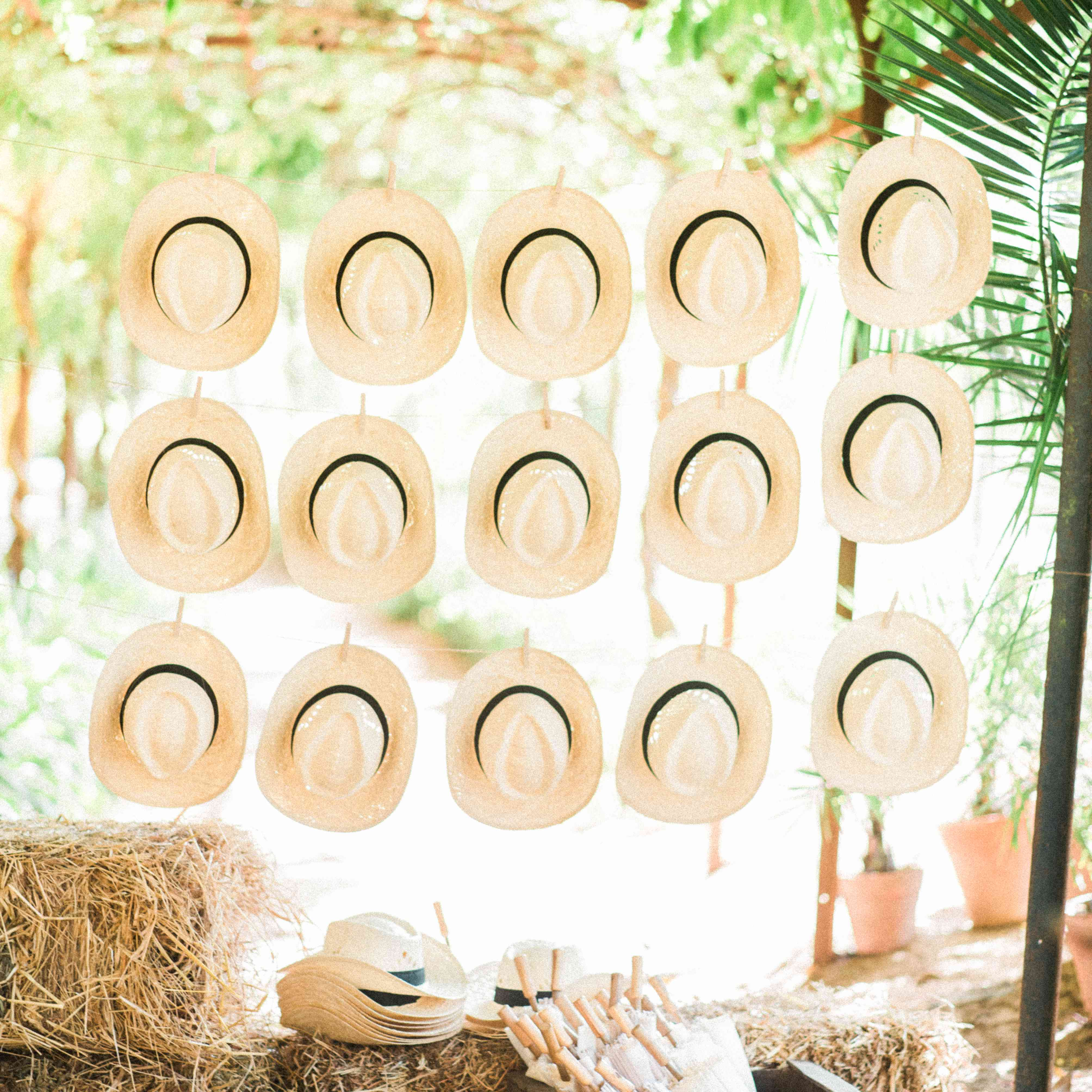 A hanging wall of straw fedora wedding favors