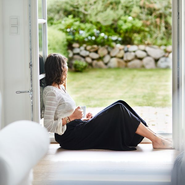Young woman sitting in doorway looking out