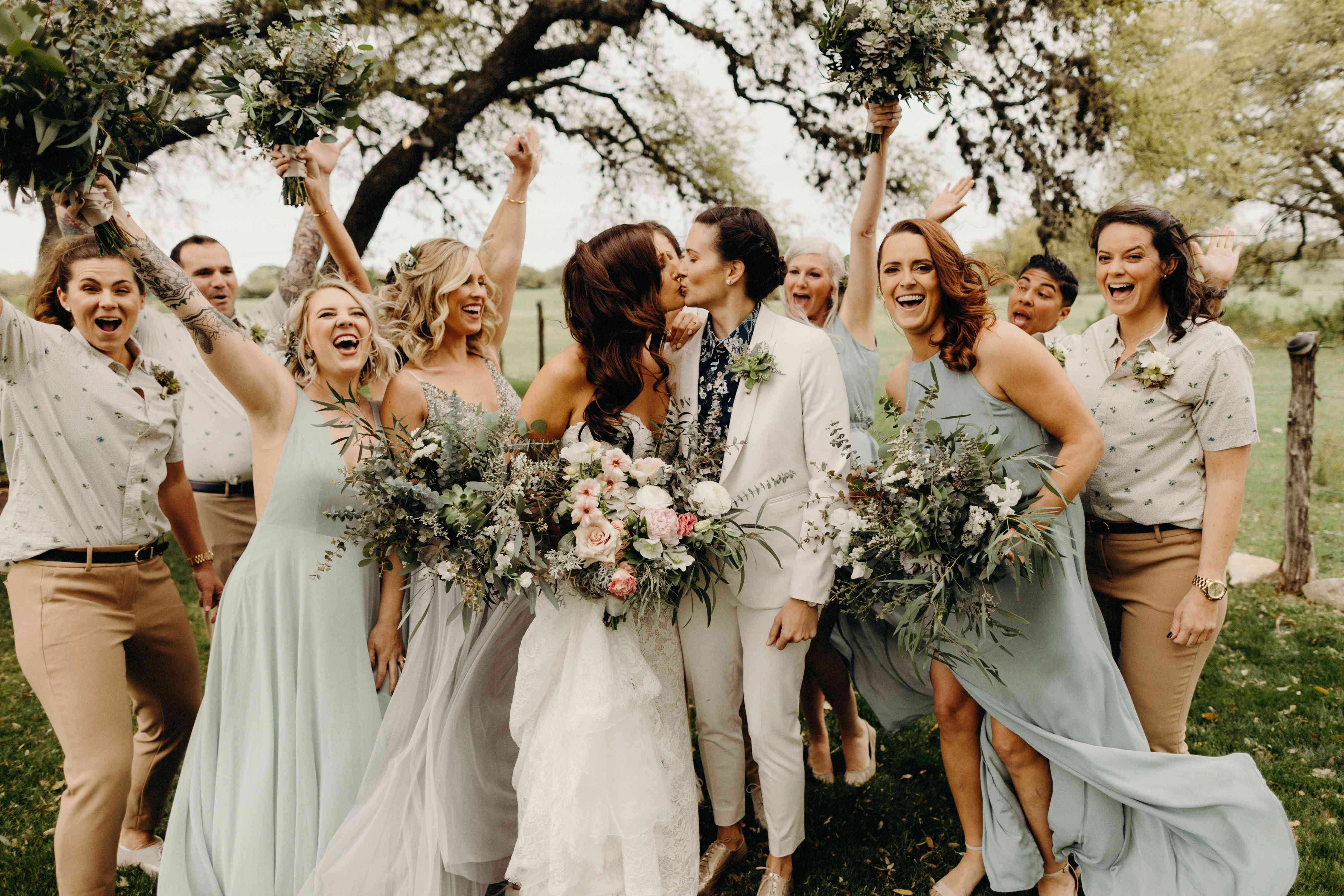 brides kissing with wedding party
