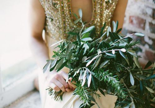 Woman holding bouquet of greenery.