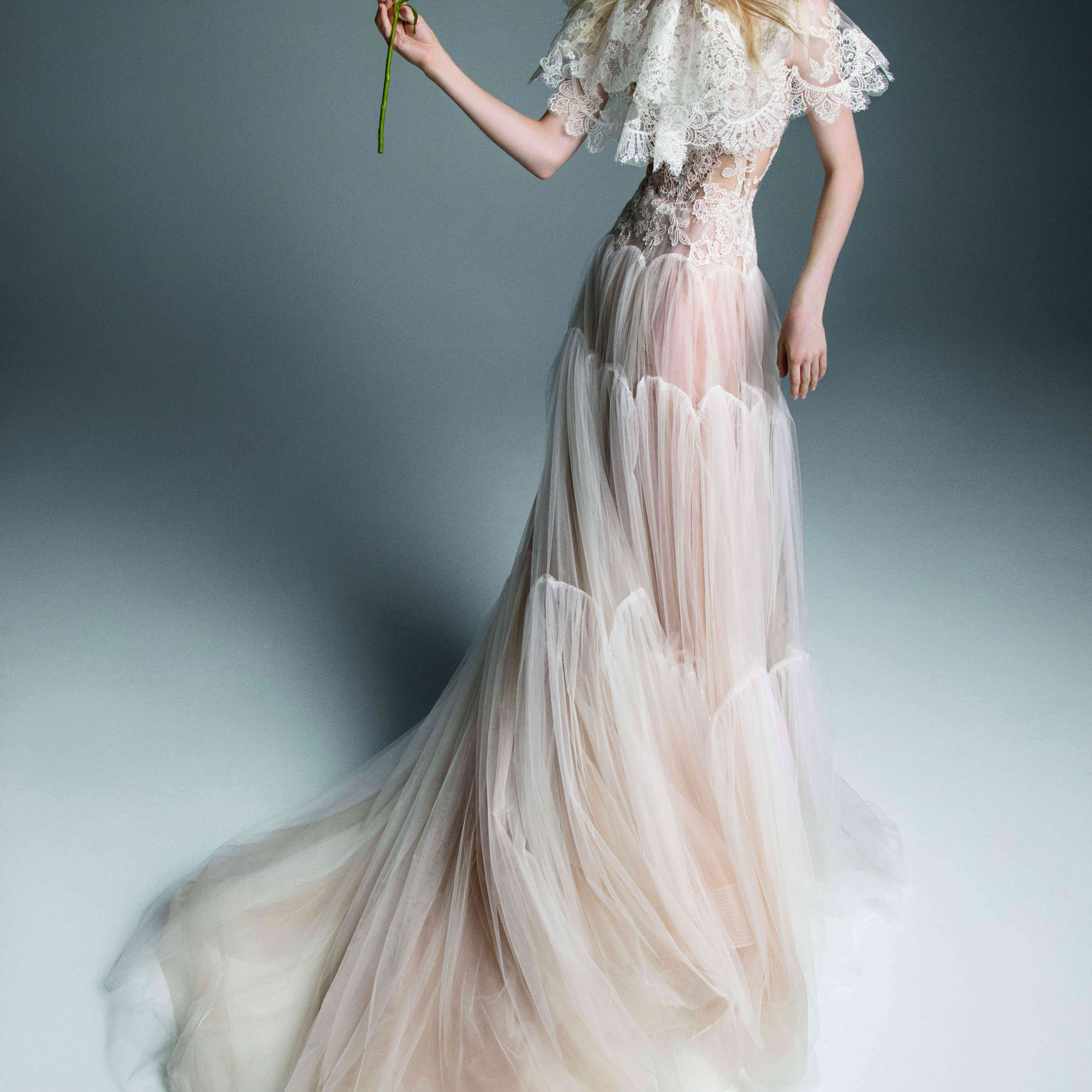 Model in tiered tulle gown with lace accents and a lace capelet