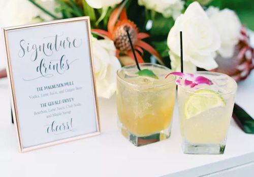 Two cocktails with a signature drinks sign