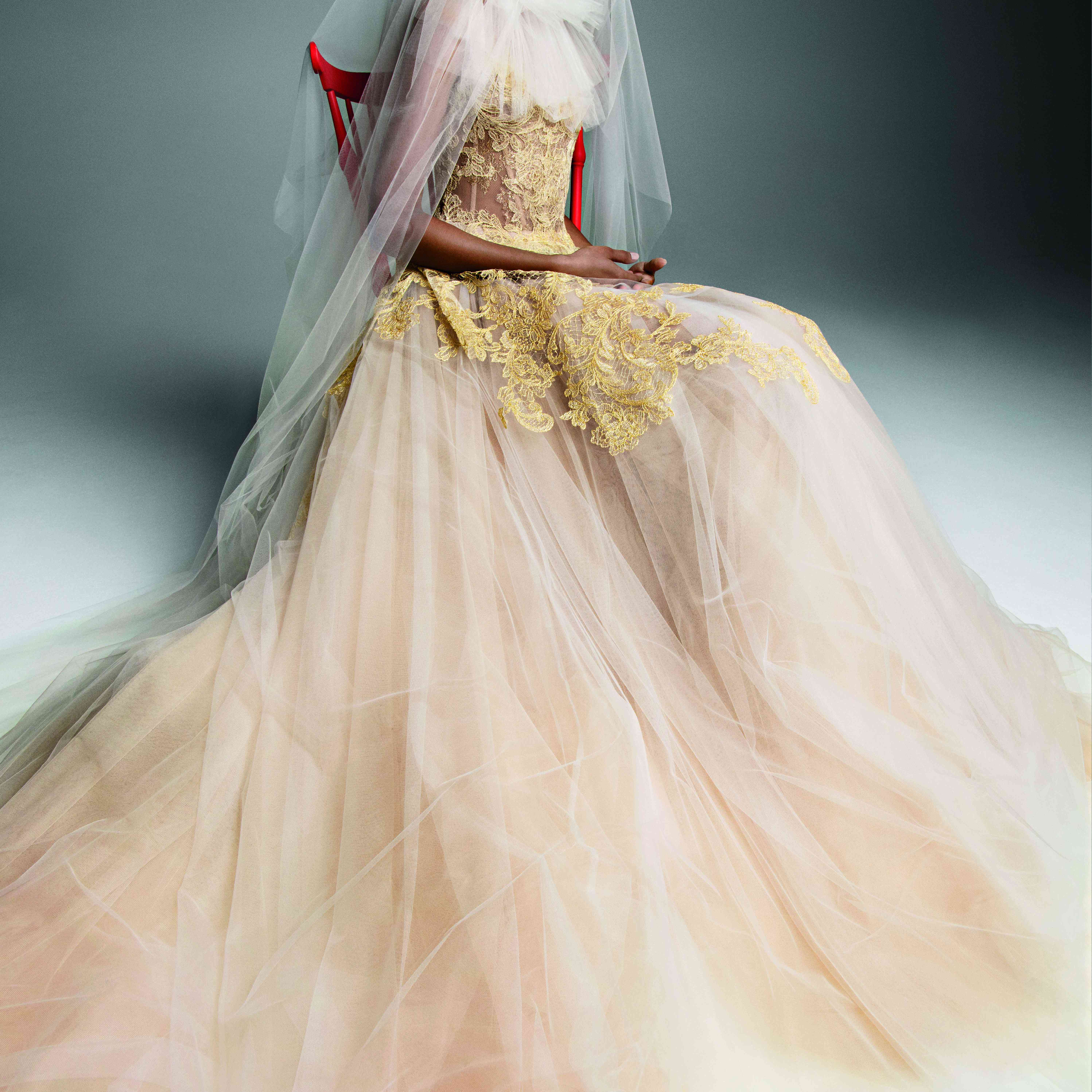 Model in nude and ivory tulle A-line gown with gold lace accents on the bodice and skirt