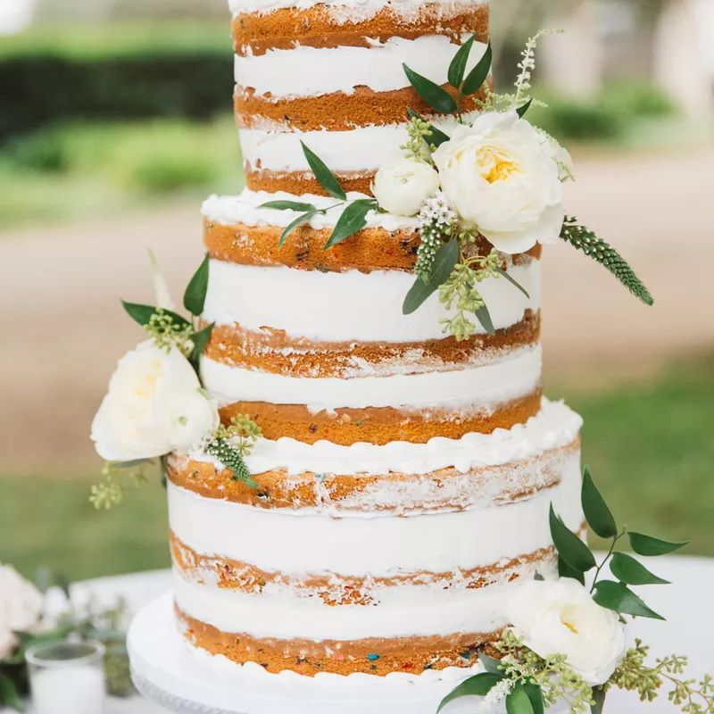 Tall white layered naked cake with white flowers