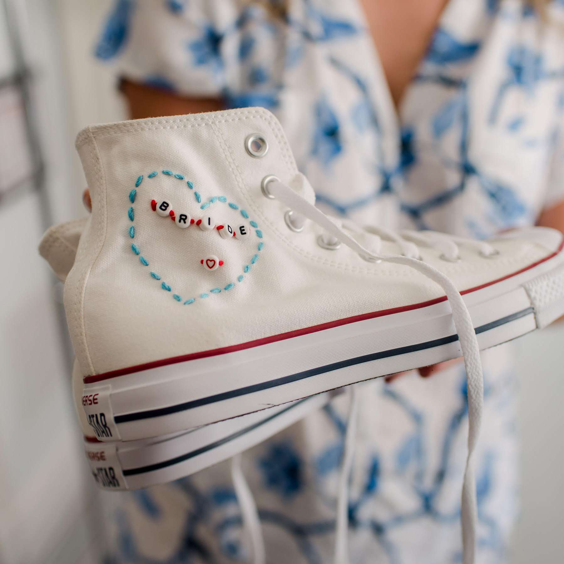 Bride holding a white Converse sneaker with