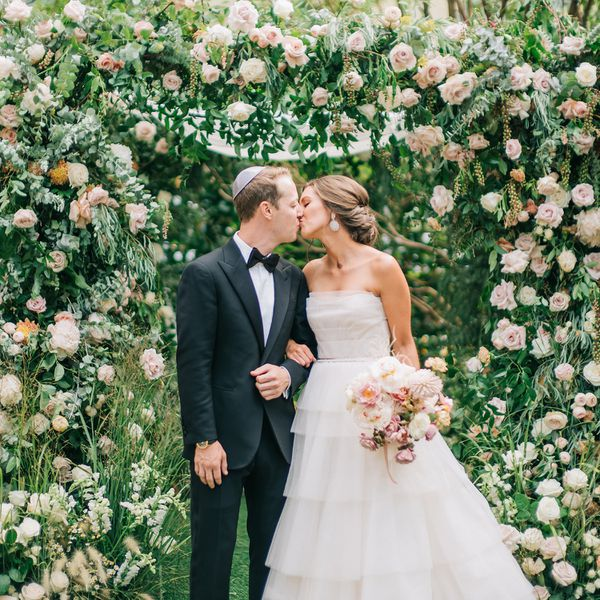 Bride and groom kissing under floral arch