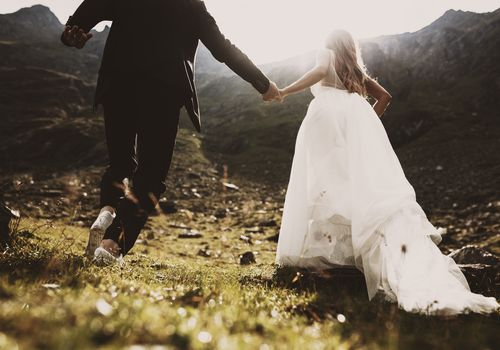 Groom and bride running up on the mountains against sunset by holding hands