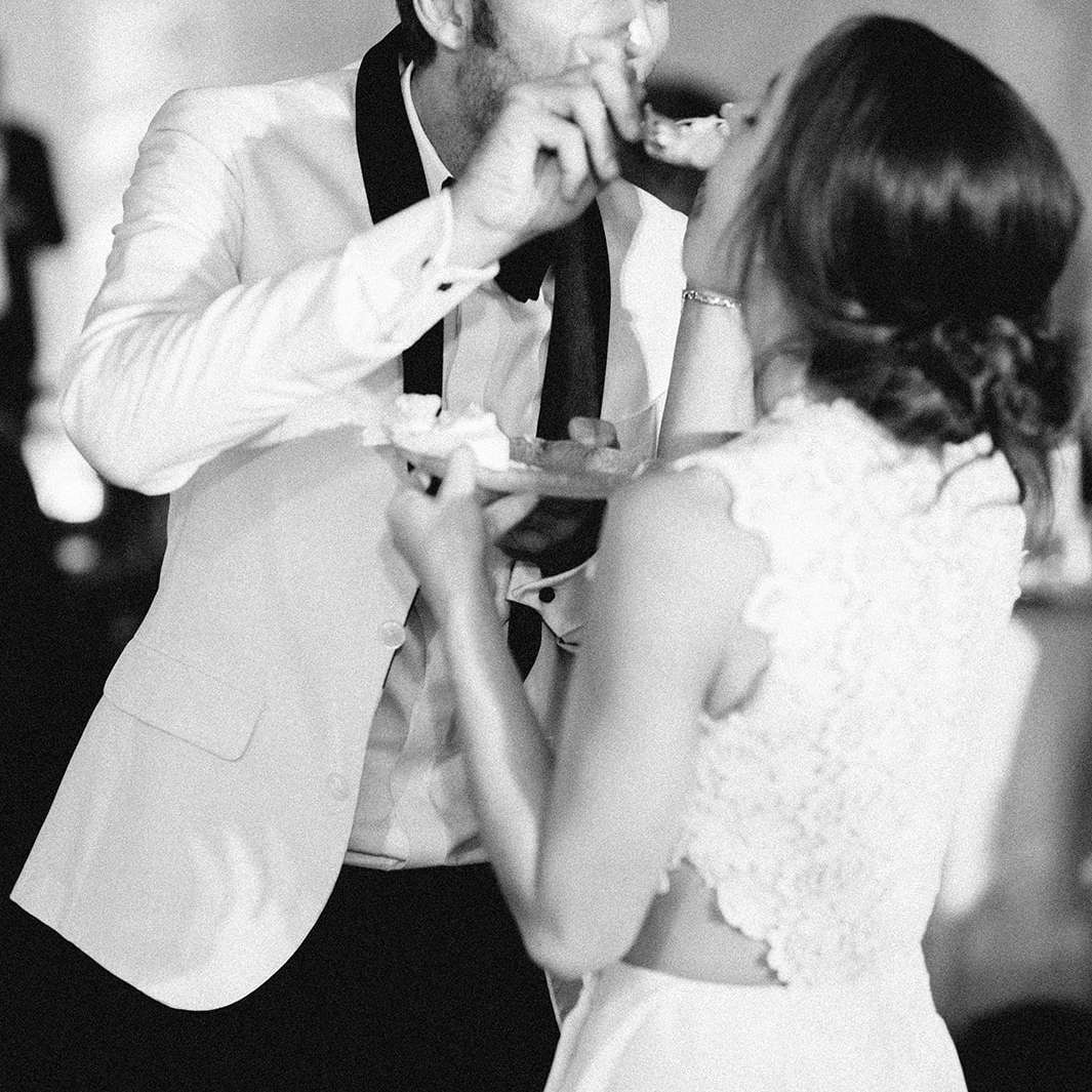 The couple feeds each other cake.