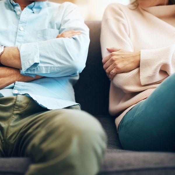 Man and woman sitting on couch crossing arms