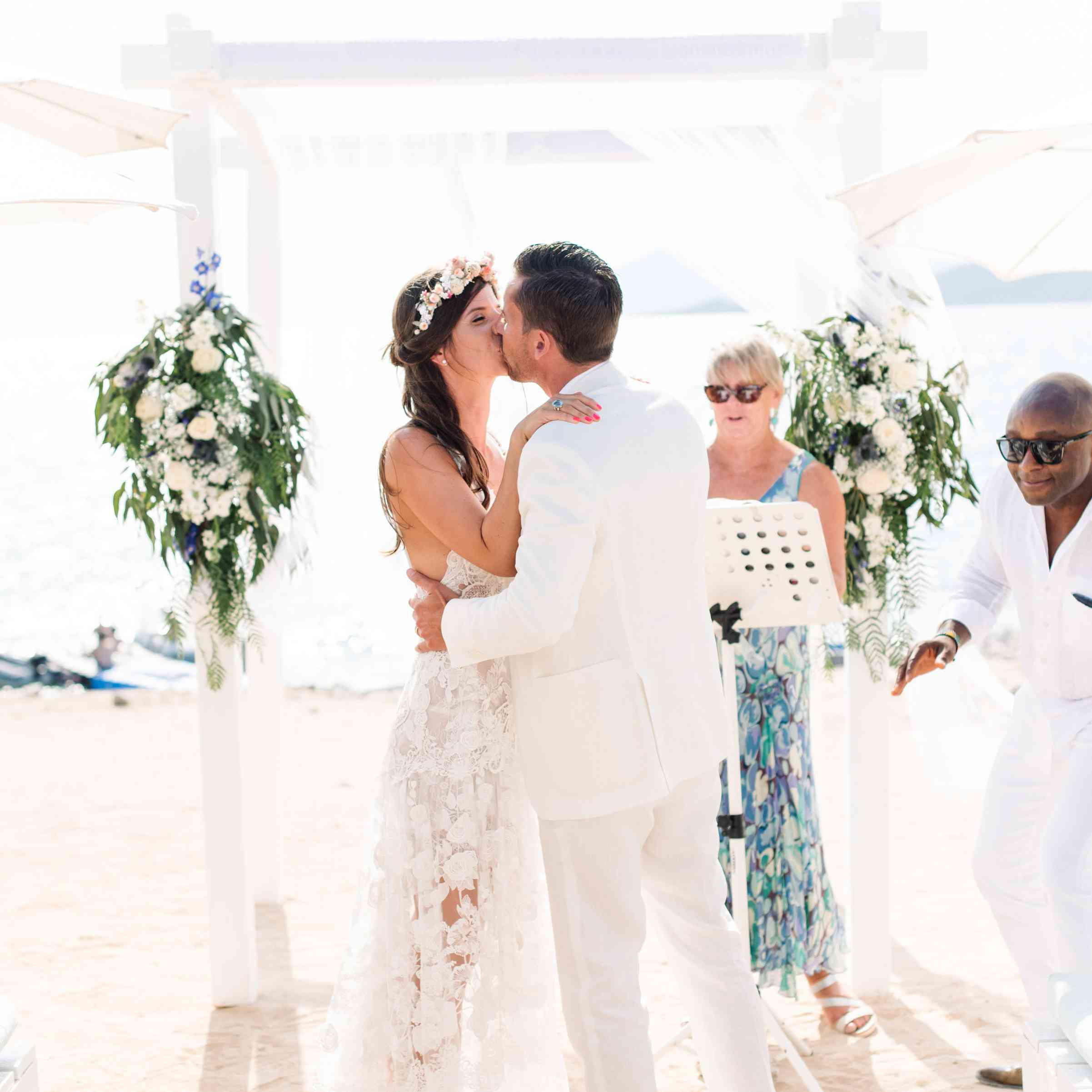 Bride and groom kiss at beach ceremony
