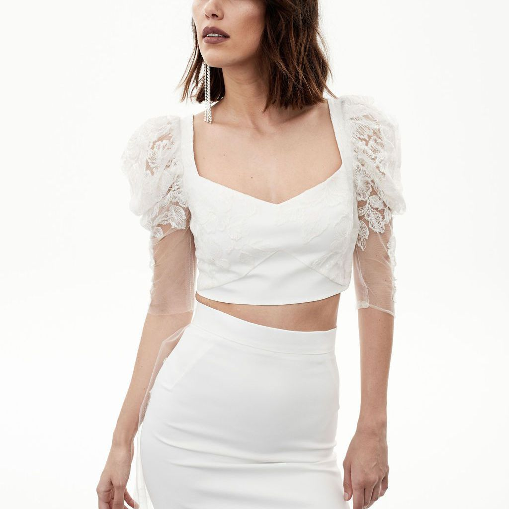 Model in crop top with lace puff sleeves and fitted long skirt