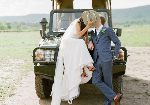 bride and groom kissing behind safari hat
