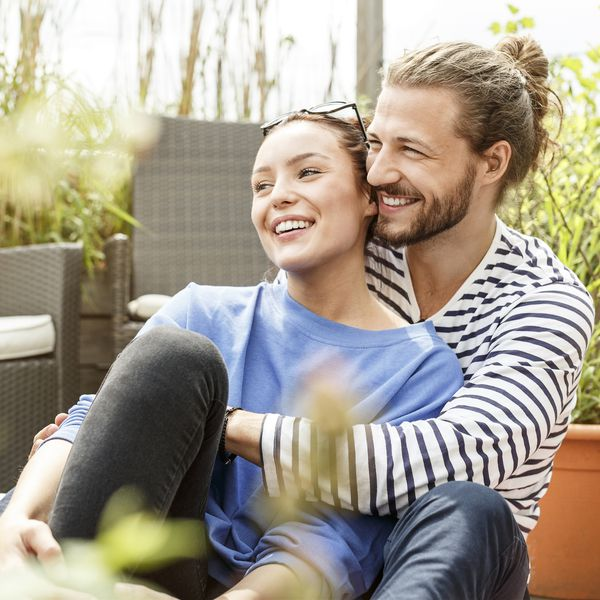 Happy couple embracing outside on a patio.