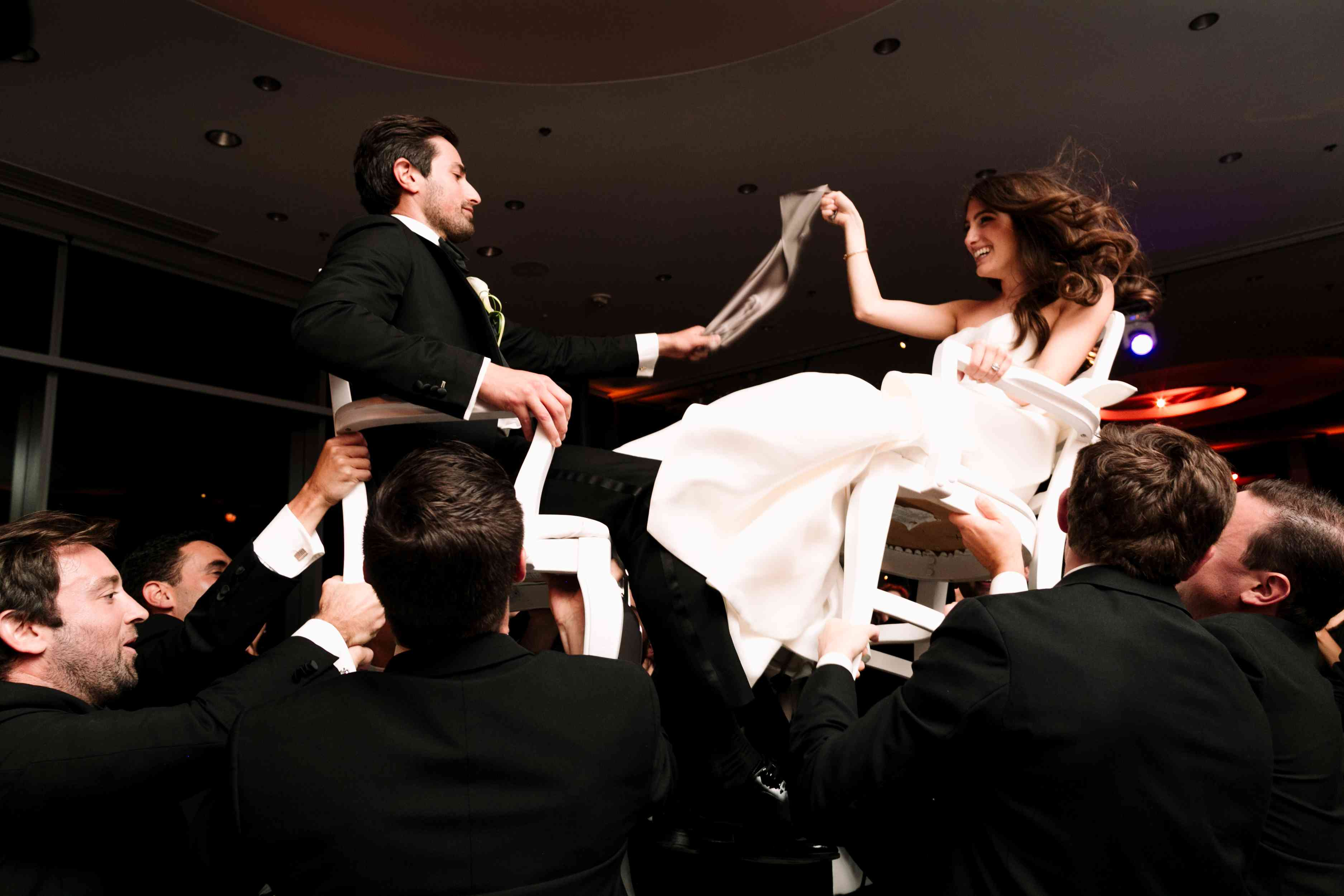 Newlyweds lifted in chairs while dancing