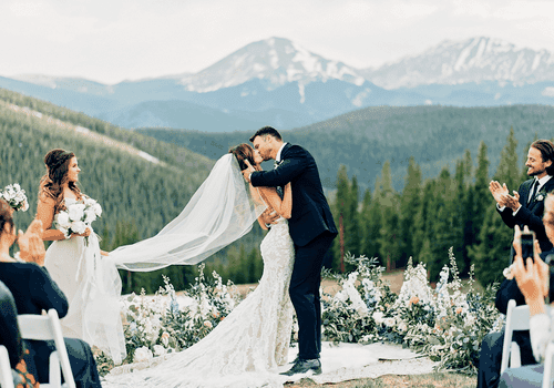 Newlyweds kissing with mountains in background