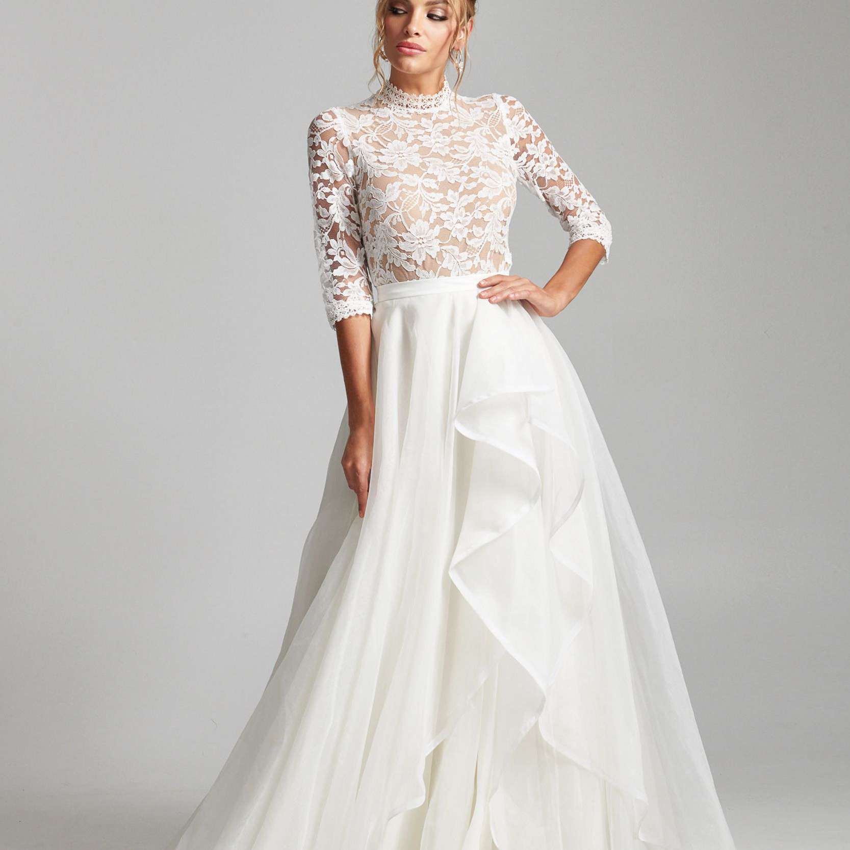 Model in high-neck three-quarter-sleeve lace top with ruffled tulle skirt