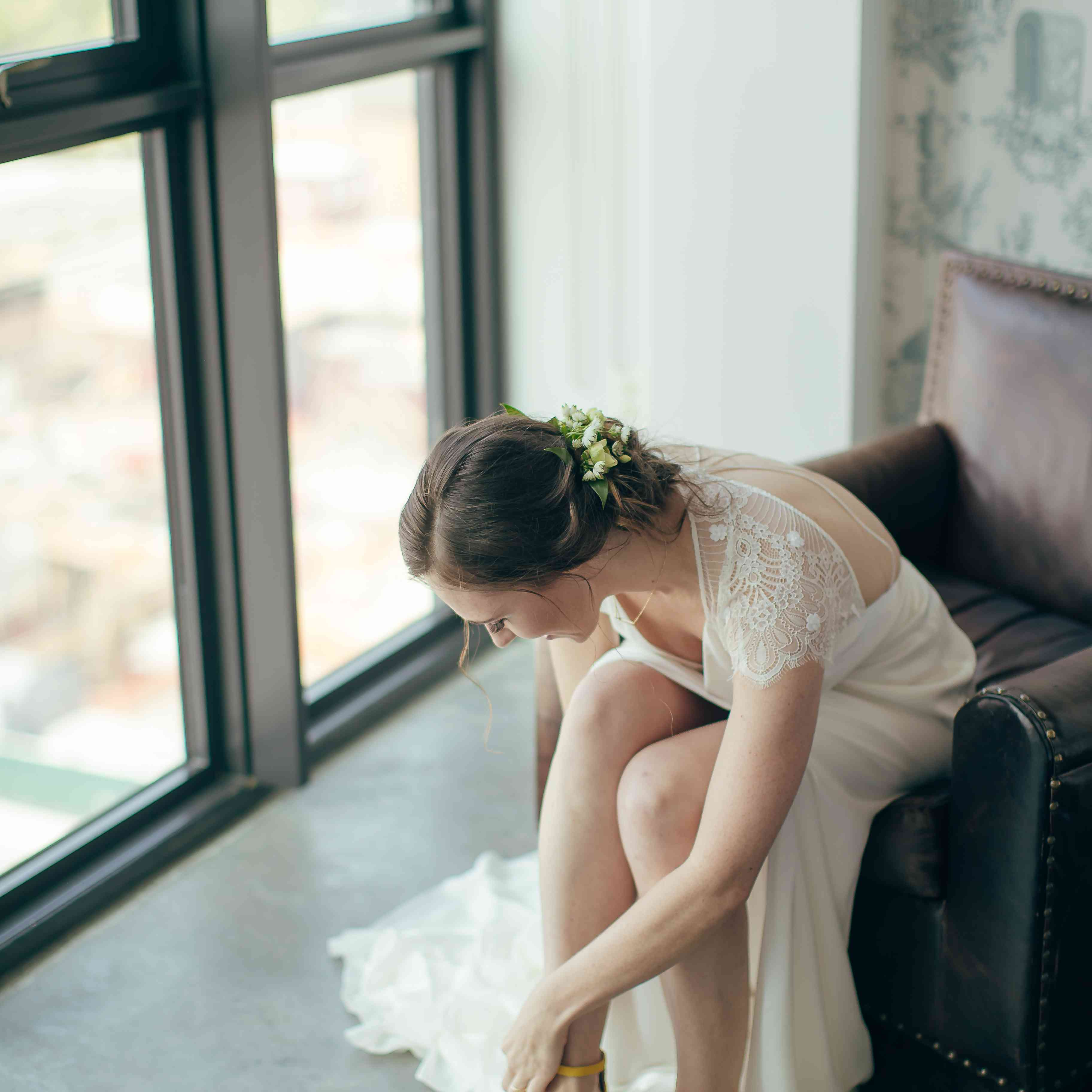 Bride putting yellow shoes on