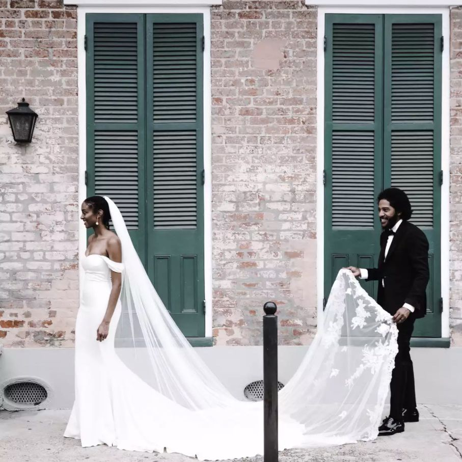 Husband carrying bride's cathedral-length veil