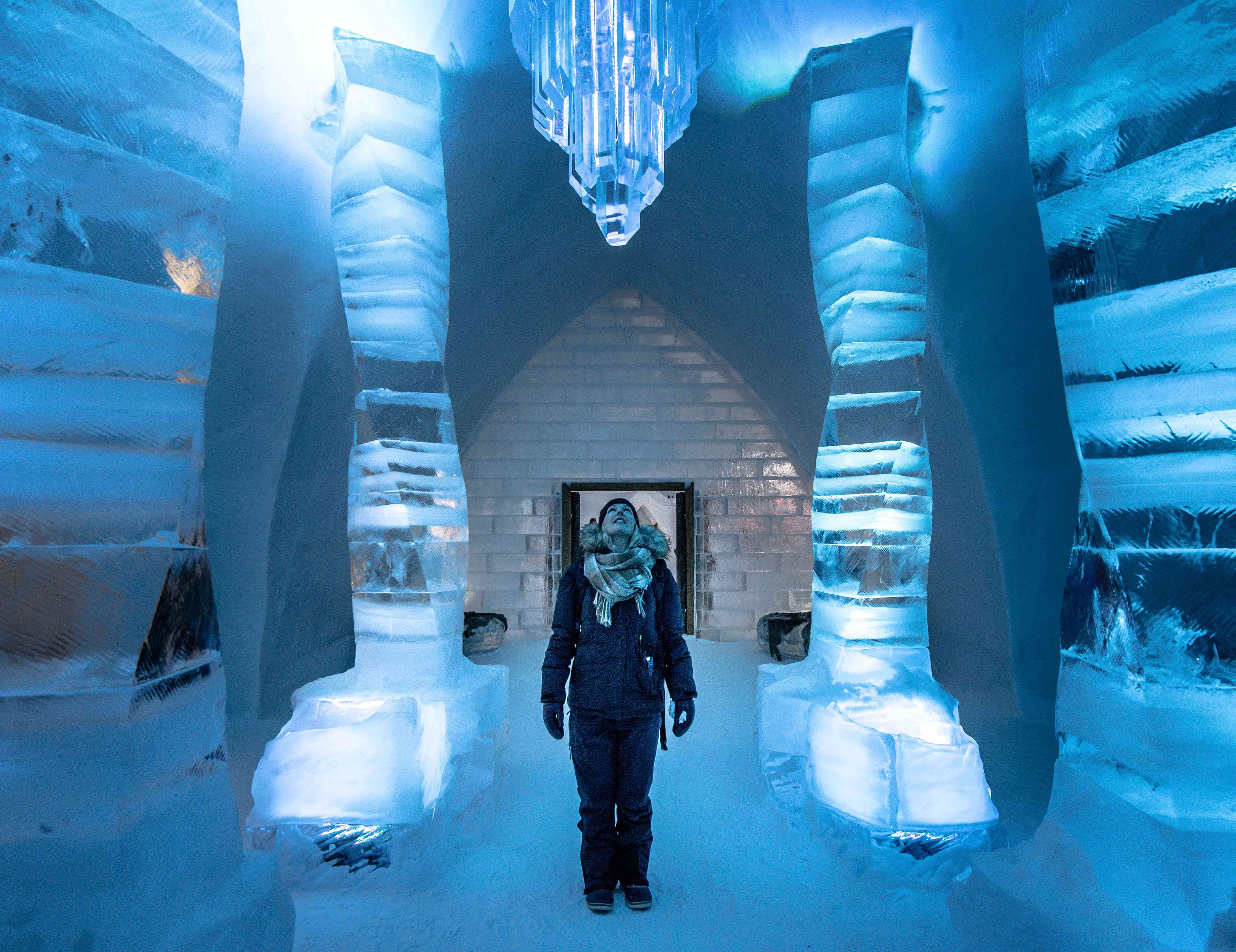 A woman looks up at an ice sculpture at Hotel de Glace