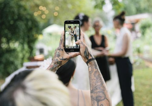 Tattoo woman using smartphone to take photo at wedding ceremony