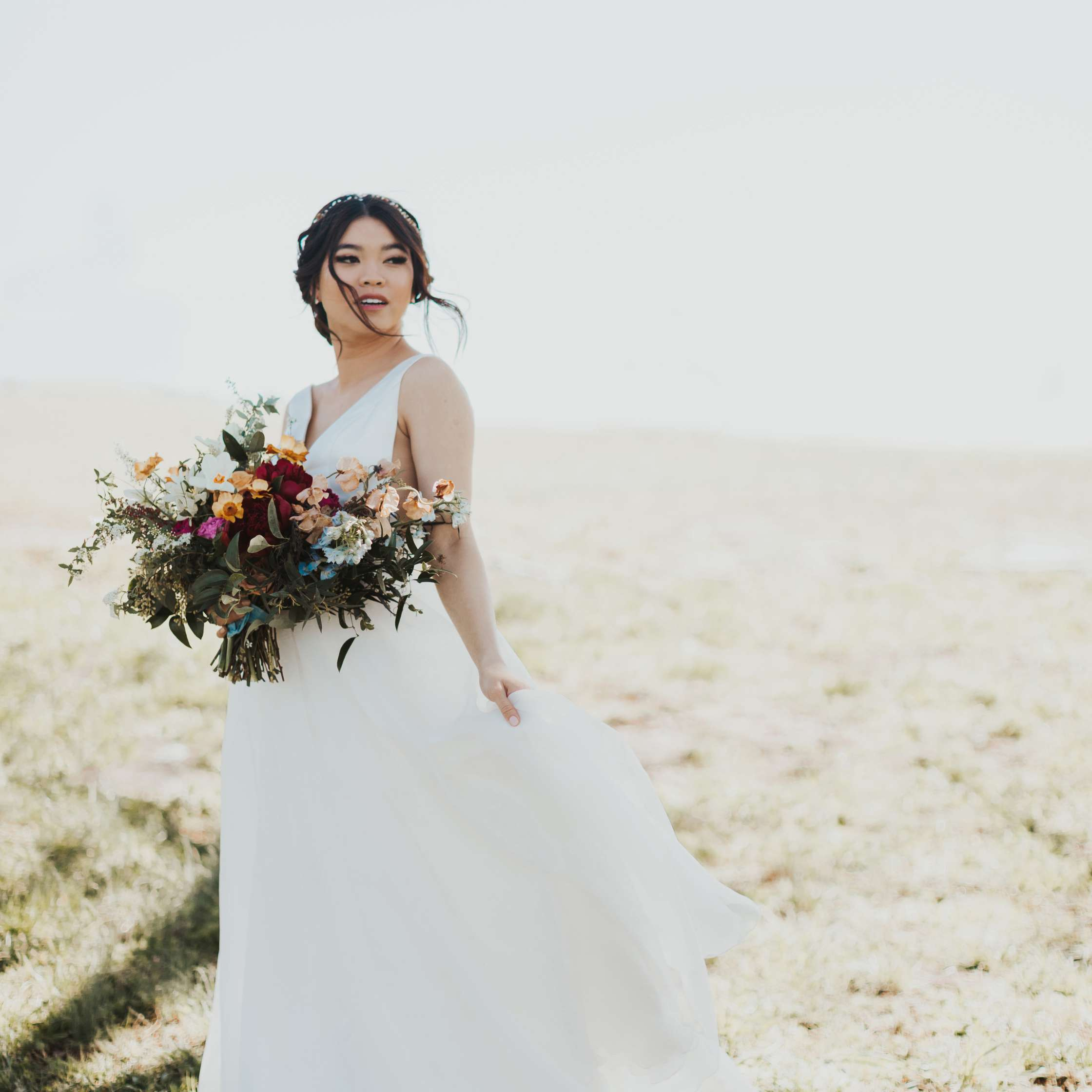 Bride standing outside holding her bouquet
