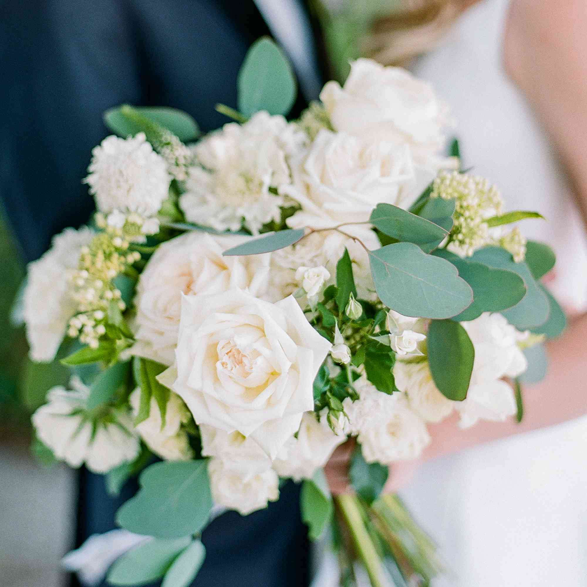 <p>Bride holding white rose bouquet</p><br><br>