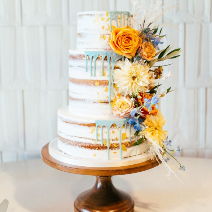 Naked cake with blue drip and fall florals